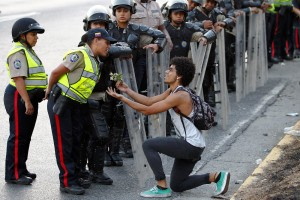 An opposition demonstrator gives flowers to a police officer as demonstrators block the city's main highway during a protest against Nicolas Maduro's government in Caracas February 14, 2014. President Maduro's government kept dozens of student protesters behind bars on Friday as unrest still rumbled across Venezuela following this week's violence at political rallies that killed three. Demonstrators gathered again in various cities, blocking roads and burning tires in some cases, to denounce the repression of protests and make a litany of complaints against Maduro ranging from rampant crime to shortages of basic products.  REUTERS/Carlos Garcia Rawlins (VENEZUELA - Tags: POLITICS CIVIL UNREST)
