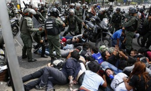 """National guards detain a group of anti-government protesters during a protest against Venezuelan President Nicolas Maduro's government in Caracas May 14, 2014. Venezuela's opposition warned that talks with Maduro's government are """"in crisis"""" due to repression of student demonstrations and officials' refusal to grant concessions that could defuse three months of street protests. Ramon Guillermo Aveledo, head of the opposition umbrella group MUD, said Socialist Party leaders have undermined the dialogue with constant insults and a refusal to consider amnesty for opposition-linked prisoners. REUTERS/Carlos Garcia Rawlins (VENEZUELA - Tags: POLITICS CIVIL UNREST) VENEZUELA-PROTESTS/"""