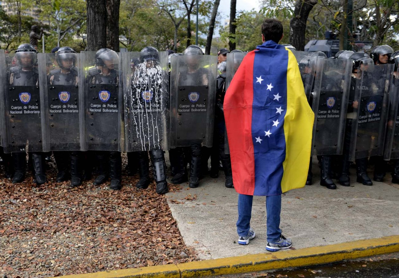 A Venezuelan student stands in front of riot police during a protest against the government of President Nicolas Maduro, in Caracas on March 12, 2014. A young man was shot dead in a confused event during protests in the city of Valencia, in northern Venezuela. About 3,000 Venezuelan students marched Wednesday to mark a month since the first deaths in anti-government protests that have now claimed at least 22 lives.  AFP PHOTO/LEO RAMIREZ