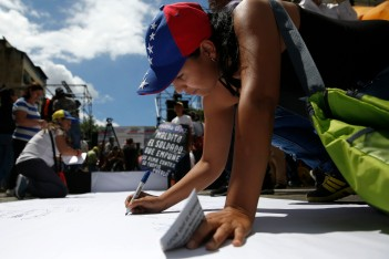 Opposition supporters sign a billboard during a gathering to protest against the Venezuelan government and in support of jailed opposition leaders Leopoldo Lopez and Antonio Ledezma in Caracas February 28, 2015. REUTERS/Carlos Garcia Rawlins (VENEZUELA - Tags: POLITICS CIVIL UNREST)