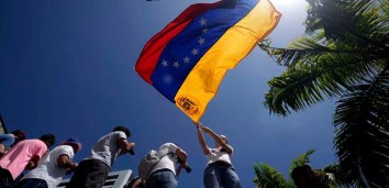 An anti-government student waves a Venezuelan flag during a protest rally in Caracas on February 16, 2014. Supporters and opponents of Venezuela's leftist government have been staging rival rallies amid spiraling discontent at the country's stubborn inflation and shortage of basic goods. Two anti-government protesters and a pro-Maduro demonstrator died in a rally early this week. AFP PHOTO/JUAN BARRETO