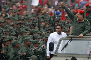 Venezuela's President Hugo Chavez greets militia members as he arrives for a ceremony to commemorate the eighth anniversary of his return to power after a brief coup, in Caracas April 13, 2010. Chavez was briefly forced from office by military officers and opposition leaders in 2002 after clashes between demonstrators in downtown Caracas killed some 20 people in events that bitterly divided the OPEC nation for years along political lines. REUTERS/Jorge Silva (VENEZUELA - Tags: POLITICS MILITARY ANNIVERSARY)