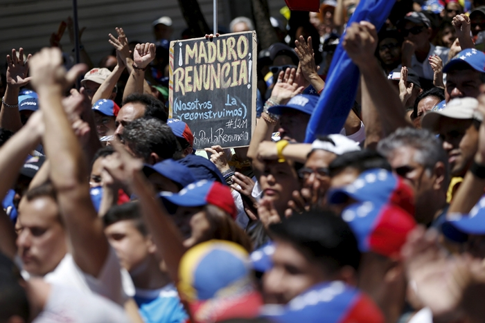 File photo of an opposition supporter holding a placard during a rally against Venezuela's President Maduro's government in Caracas