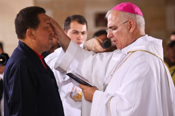 Venezuelan President Chavez receives a blessing from a bishop during a mass at the military academy in Caracas